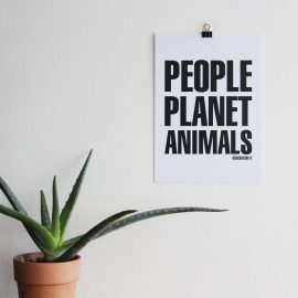 This is an image of the Generation-V Vegan PeoplePlanetAnimals Poster hung on a white wall next to a green aloe vera plant
